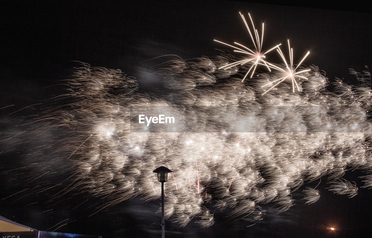night, illuminated, firework, firework display, arts culture and entertainment, celebration, exploding, event, motion, low angle view, smoke - physical structure, long exposure, firework - man made object, blurred motion, sky, glowing, light, no people, sparks, nature, sparkler