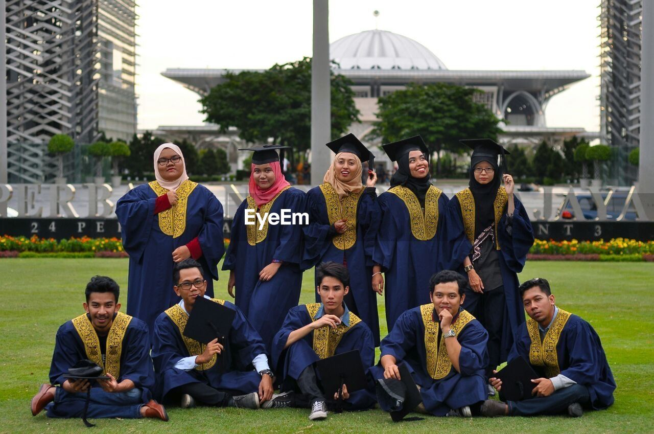 looking at camera, portrait, large group of people, grass, sitting, day, outdoors, front view, building exterior, men, young adult, architecture, full length, tree, smiling, togetherness, university, real people, group of people, standing, women, young women, campus, adult, people, adults only