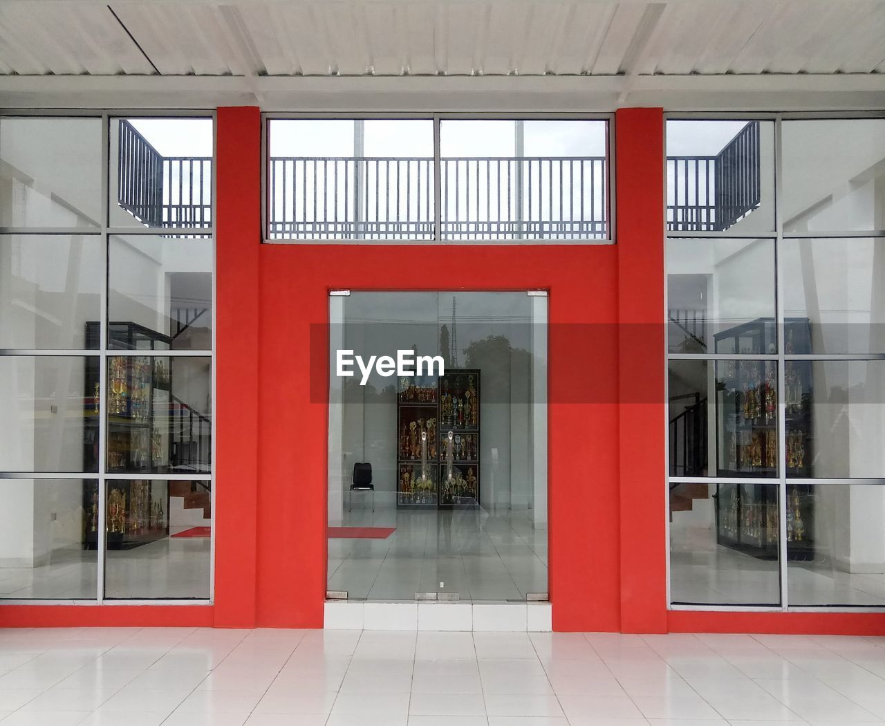 architecture, built structure, glass - material, building, red, window, entrance, indoors, transparent, reflection, door, flooring, no people, day, modern, arcade, corridor, absence, office building exterior, glass, tiled floor