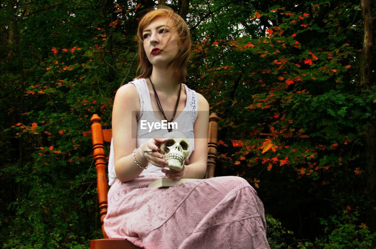 Young Woman Sitting With Artificial Skull And Cigarette