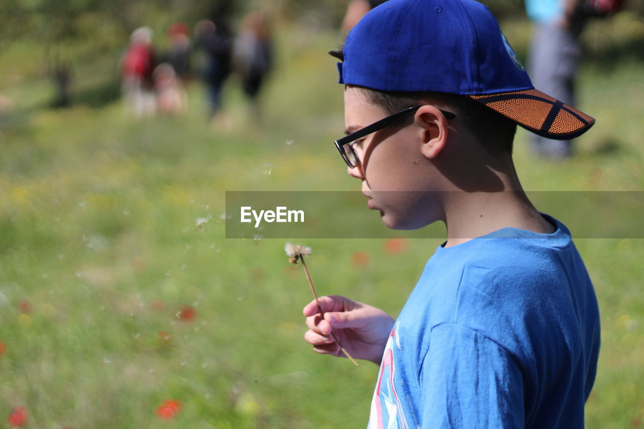 Close-Up Of Boy Blowing Dandelion Seeds