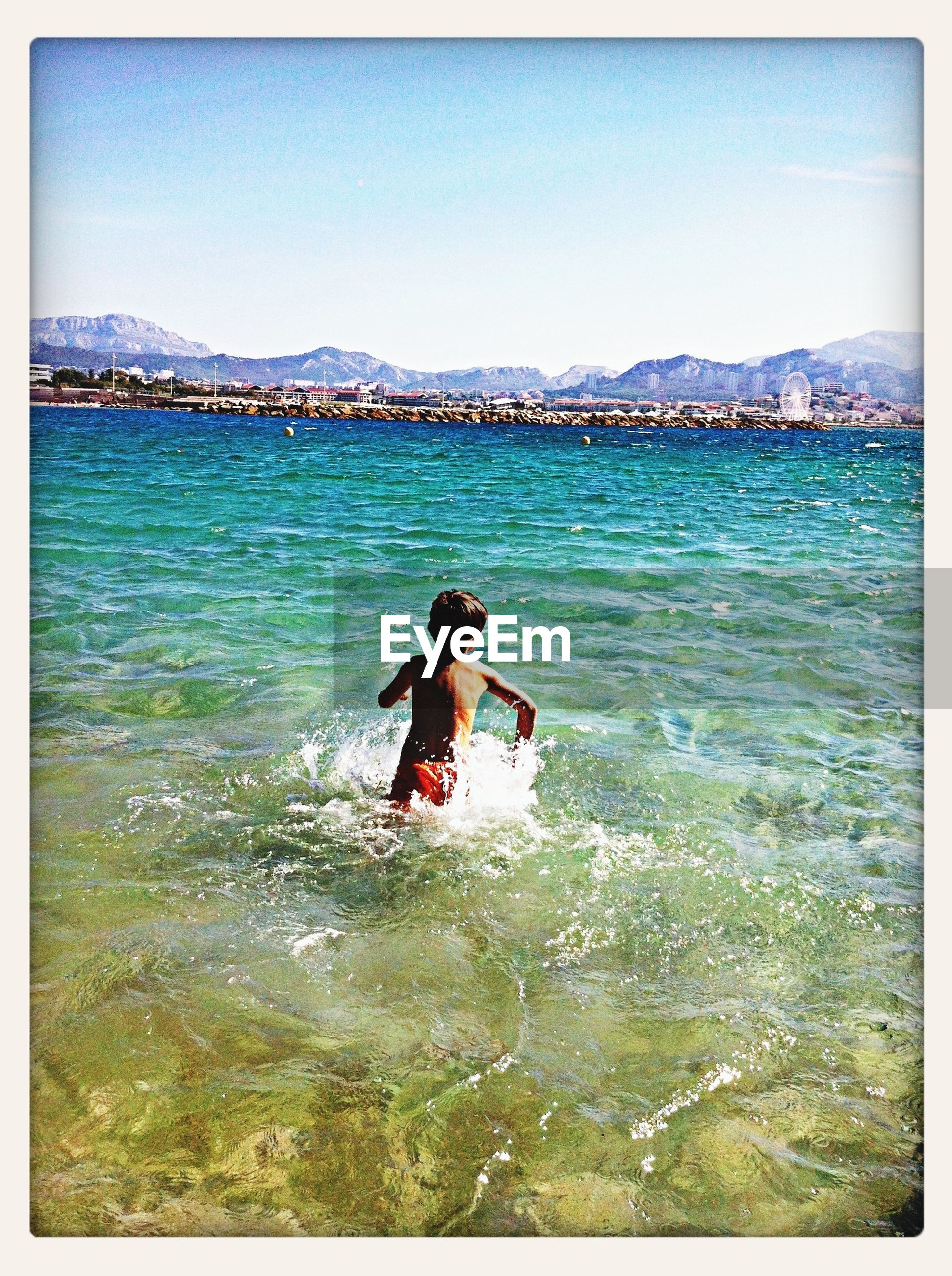 Rear view of boy playing in sea against sky