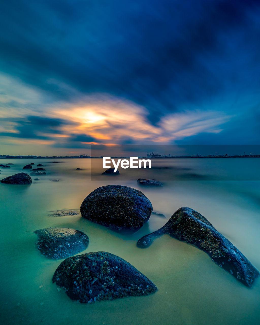 ROCKS IN SEA AGAINST SUNSET SKY