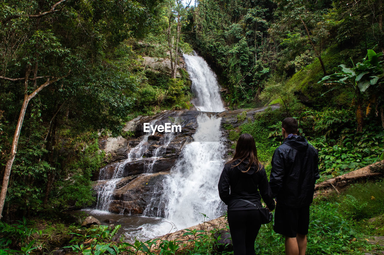 Rear view of couple looking at waterfall in forest