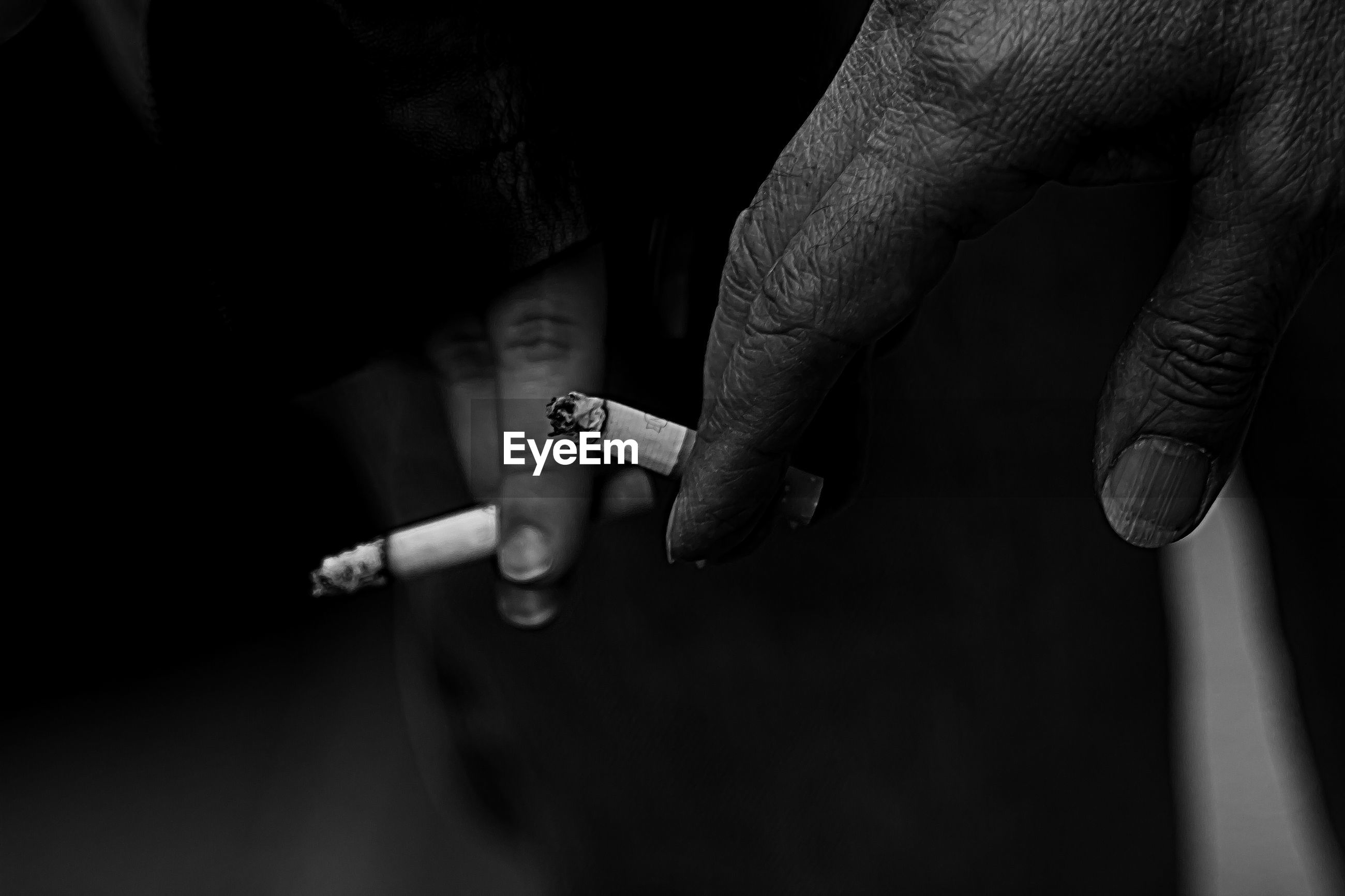 Cropped hand of people holding cigarettes