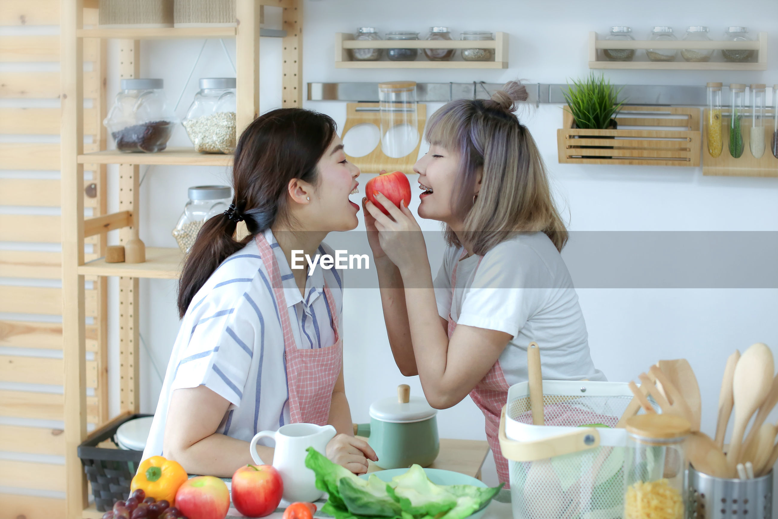 Side view of young woman holding apple at kitchen