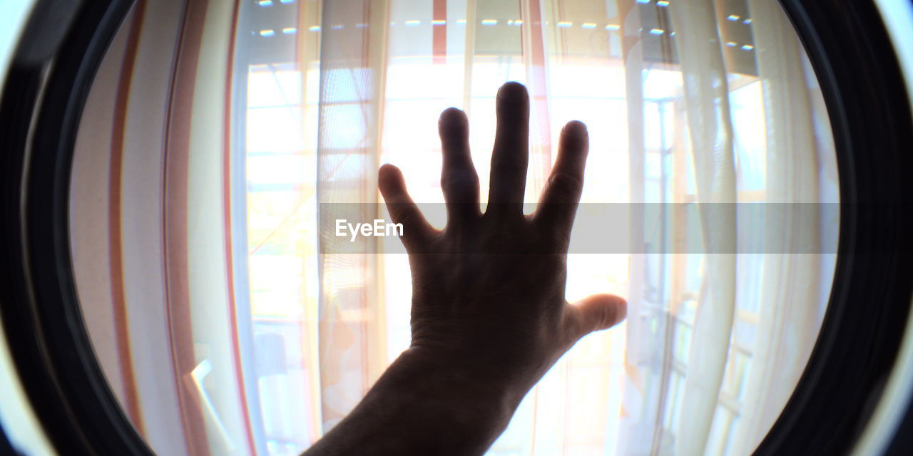 window, indoors, transparent, glass - material, human hand, human body part, hand, one person, human finger, finger, real people, curtain, day, body part, touching, sunlight, lifestyles, unrecognizable person, leisure activity