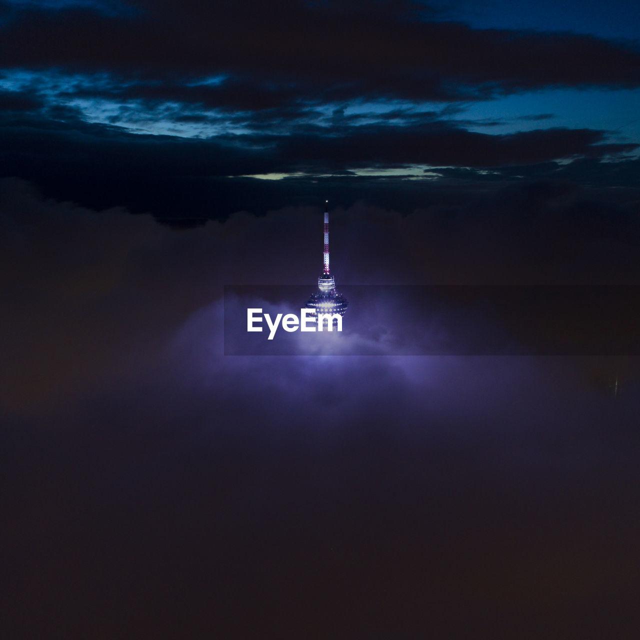 Illuminated tower against sky at night