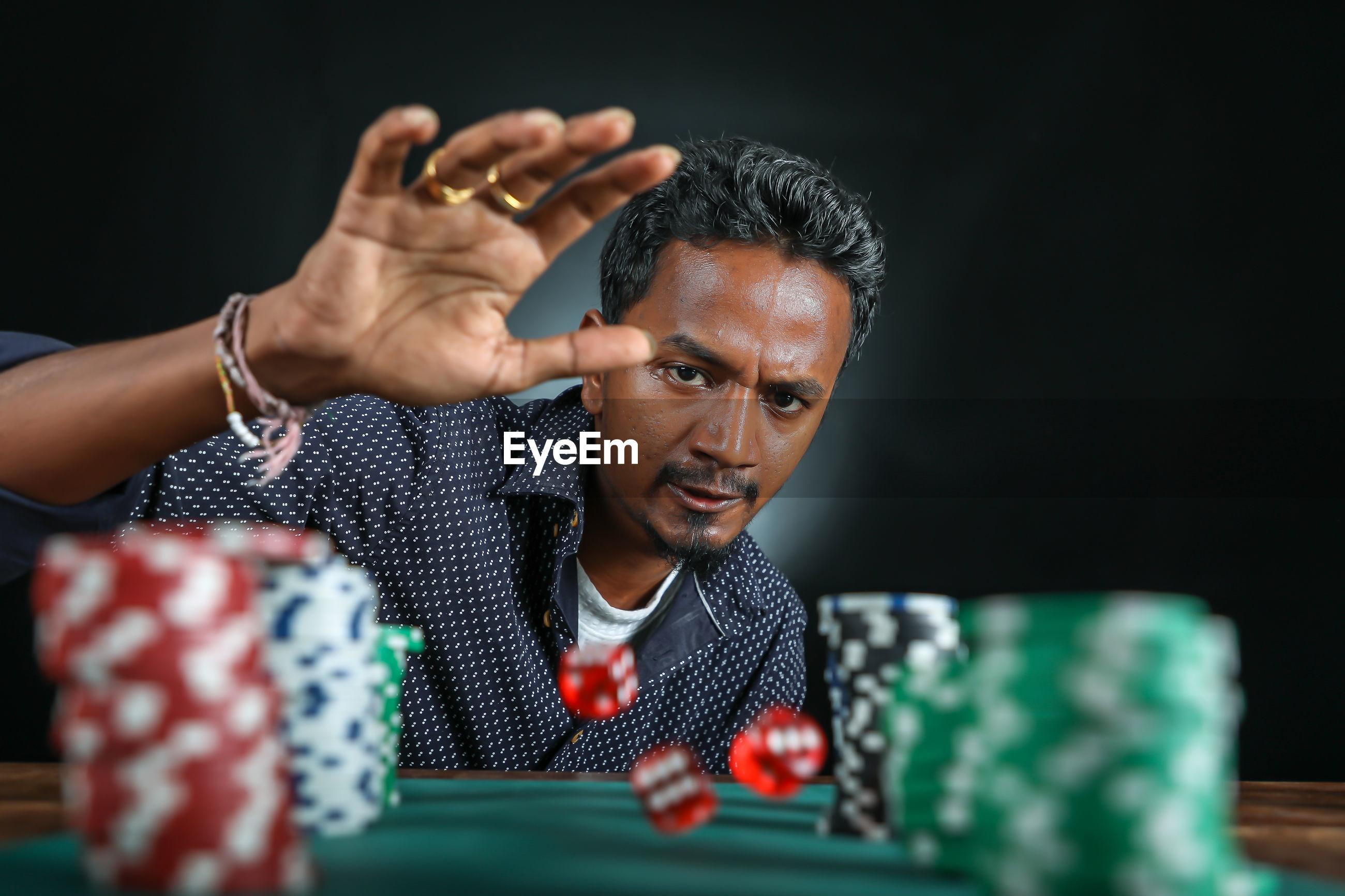 Confident mature man rolling dice at craps table against black background