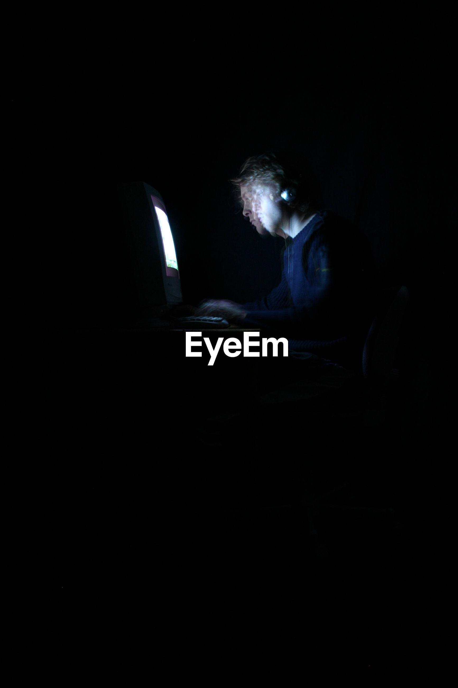 Double exposure of man working on computer in dark
