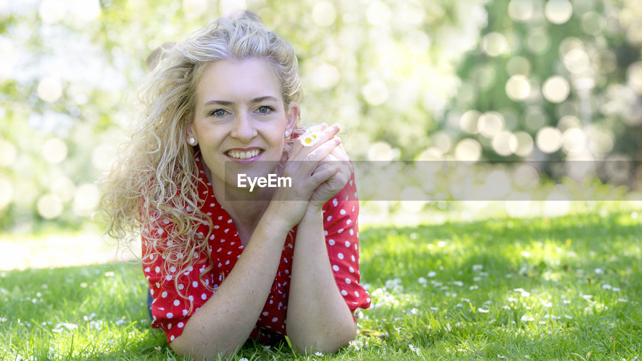 looking at camera, portrait, one person, smiling, grass, plant, happiness, women, hair, day, nature, focus on foreground, hairstyle, sitting, holding, leisure activity, blond hair, front view, beautiful woman, outdoors
