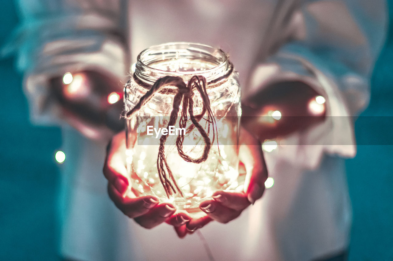 Midsection of person holding illuminated jar