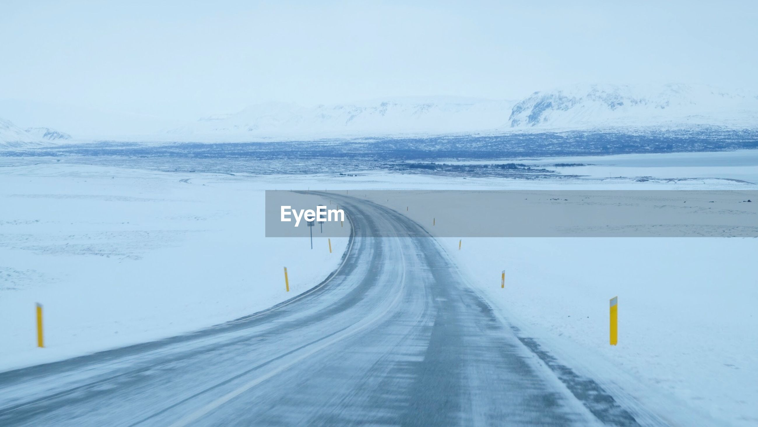 SNOW COVERED ROAD PASSING THROUGH LANDSCAPE