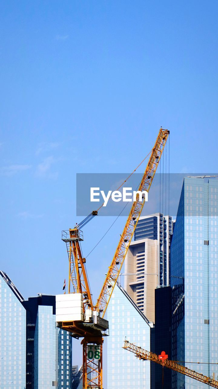 architecture, built structure, crane - construction machinery, sky, building exterior, machinery, development, construction industry, city, construction site, industry, tall - high, nature, building, no people, office building exterior, skyscraper, incomplete, day, blue, outdoors, construction equipment, modern