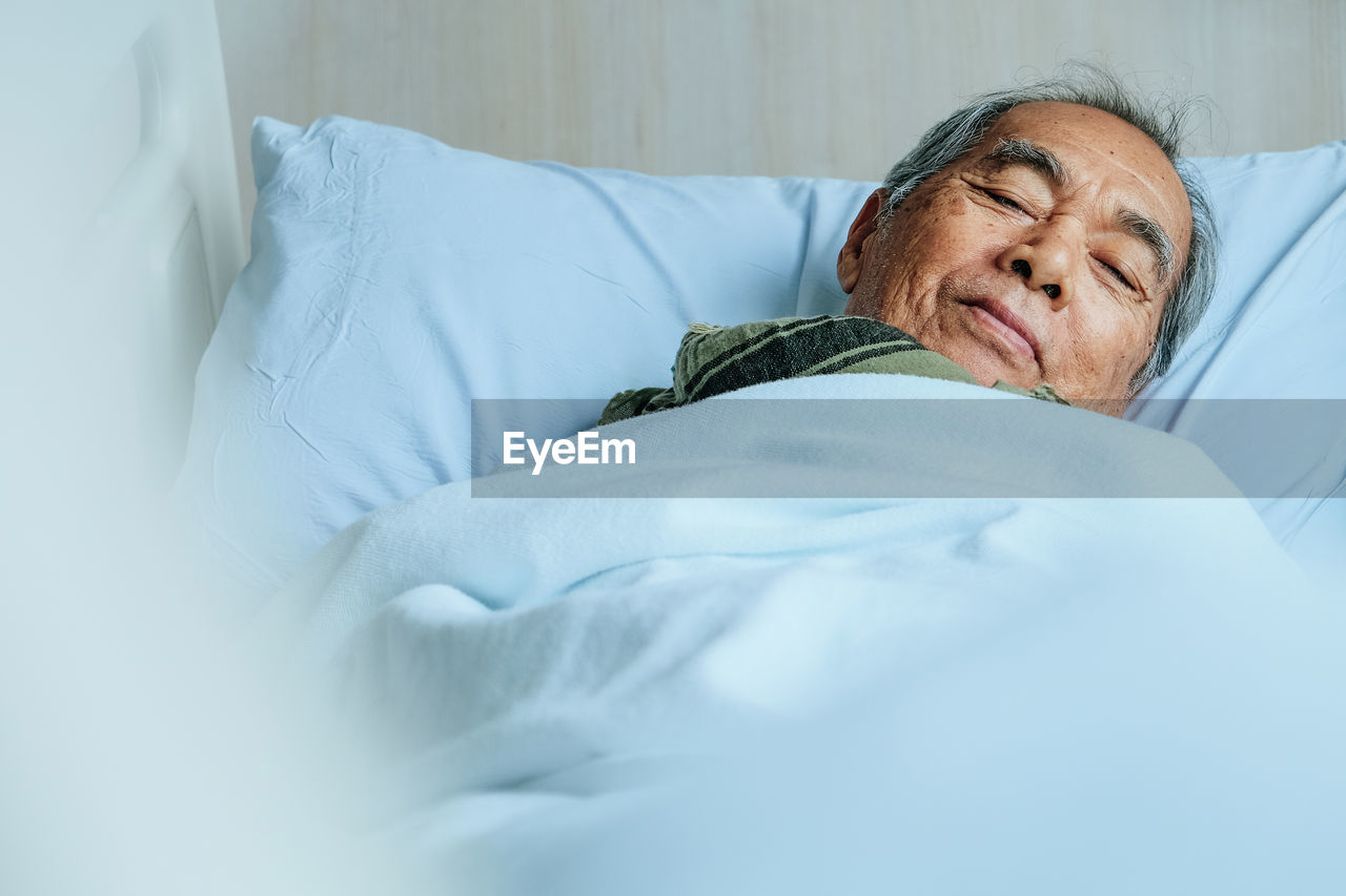 Portrait Of Senior Man Lying Down On Bed At Hospital