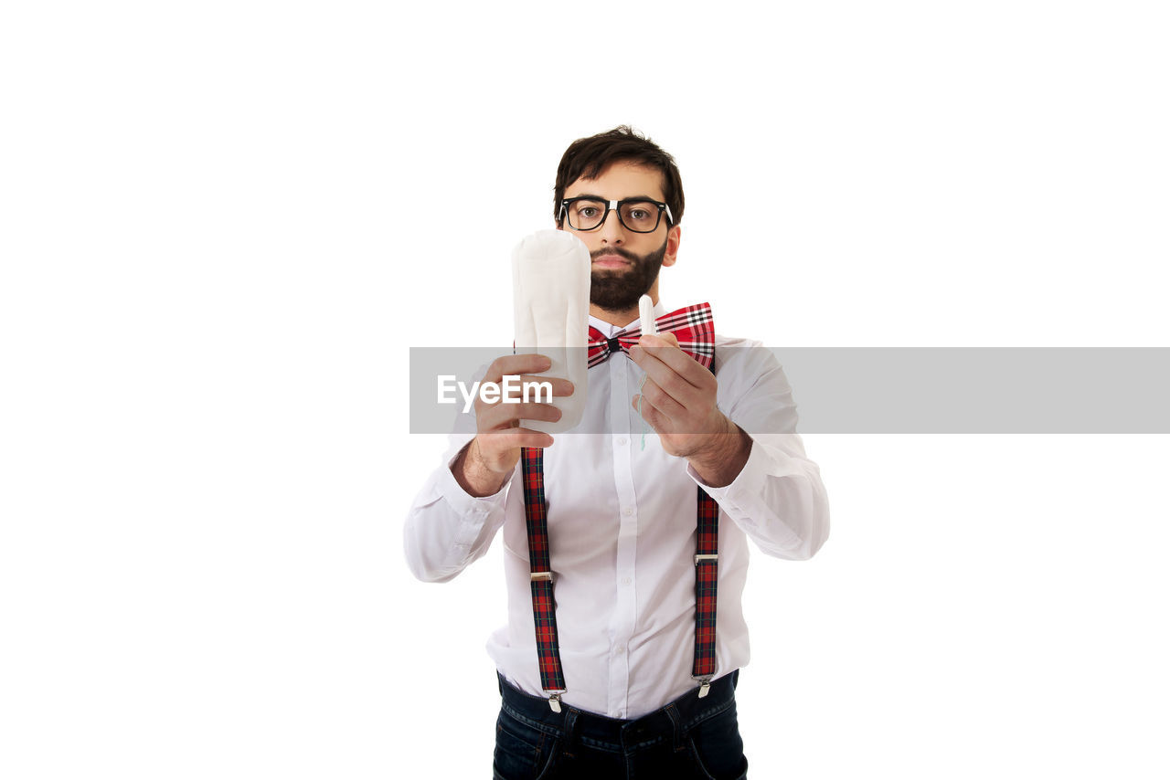 Man holding tampon and padding while standing against white background