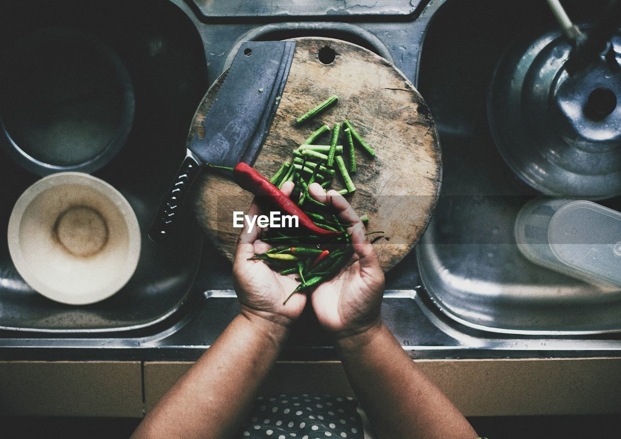HAND HOLDING CHILI AND GREEN BEANS OVER SINK