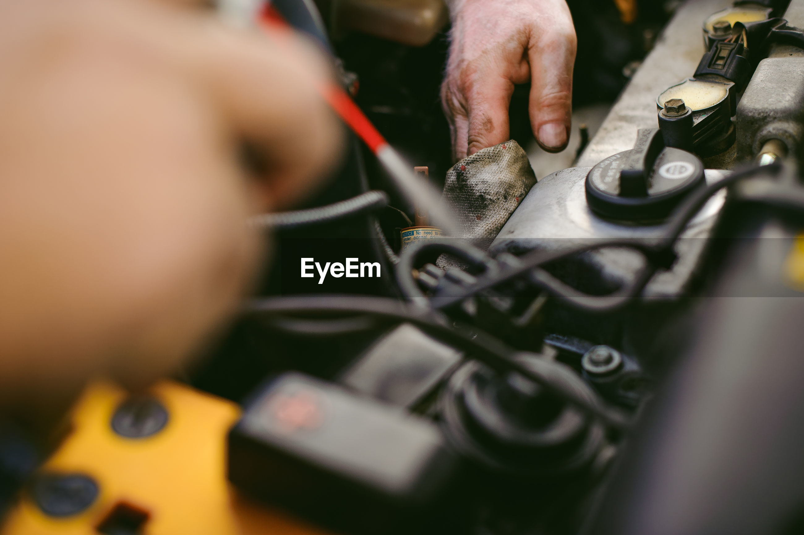 Close-up of hands repairing car engine