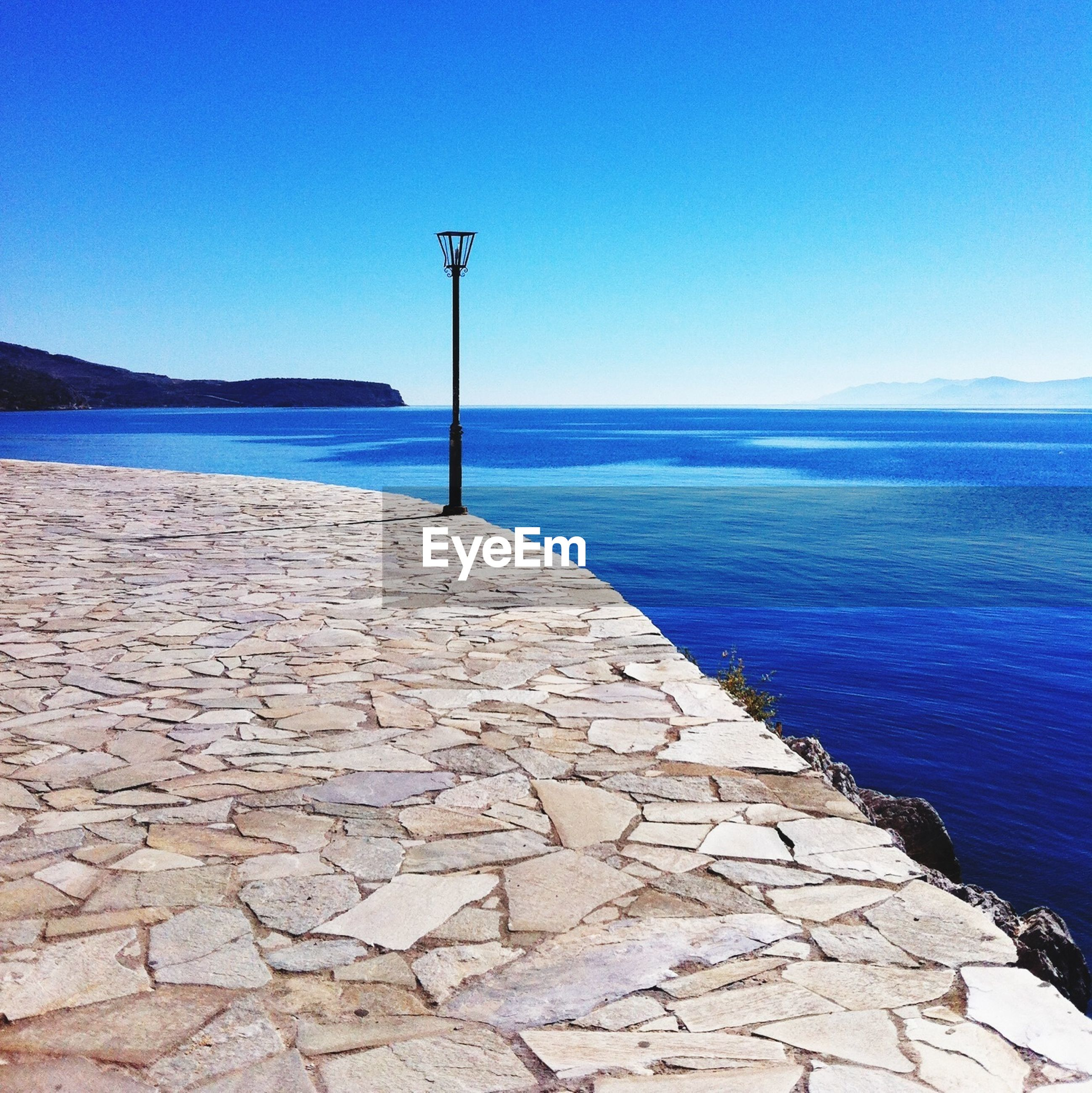 sea, water, horizon over water, blue, clear sky, tranquil scene, tranquility, copy space, scenics, beauty in nature, the way forward, street light, nature, sky, beach, idyllic, outdoors, sunlight, shore, empty
