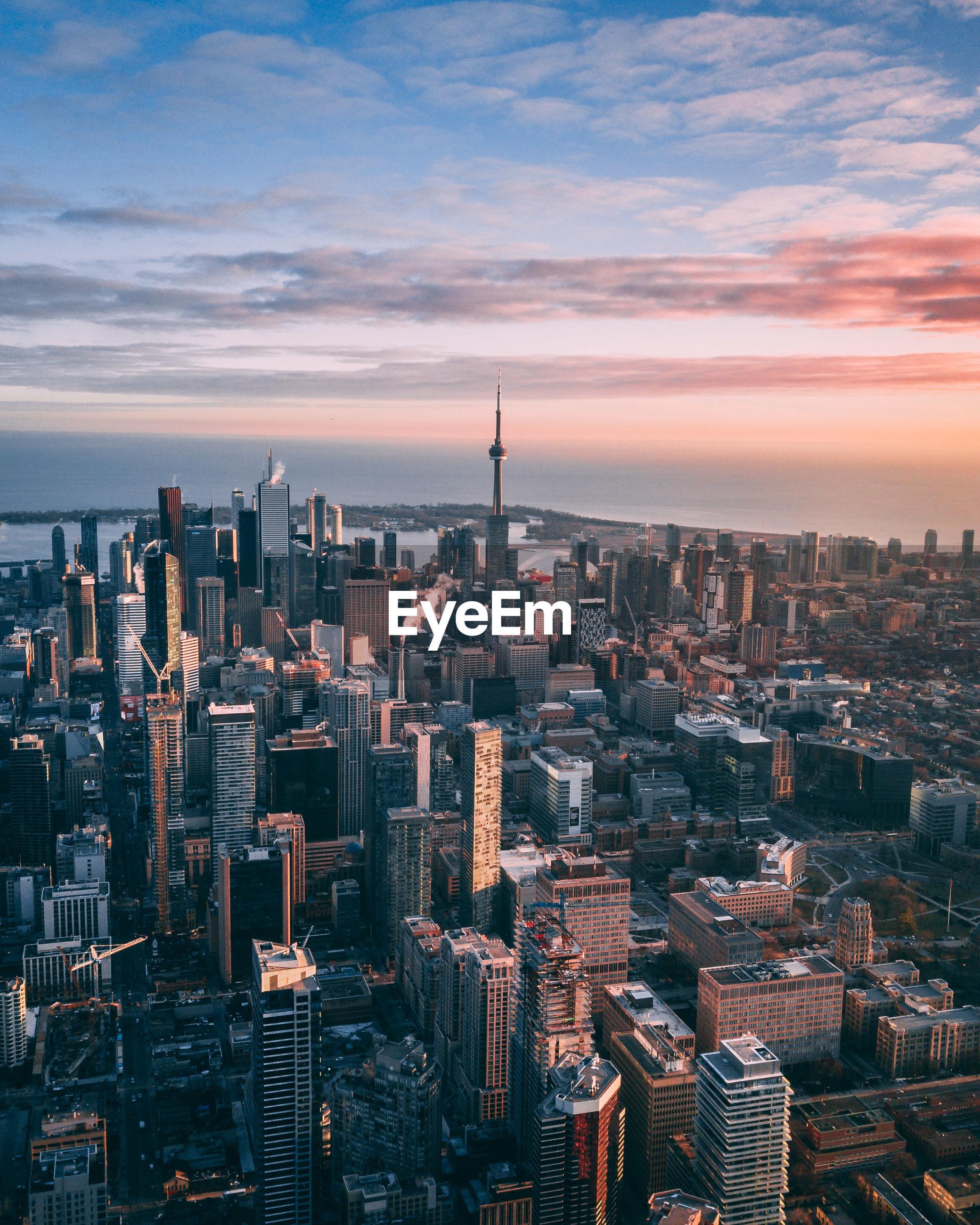 AERIAL VIEW OF BUILDINGS AGAINST CLOUDY SKY