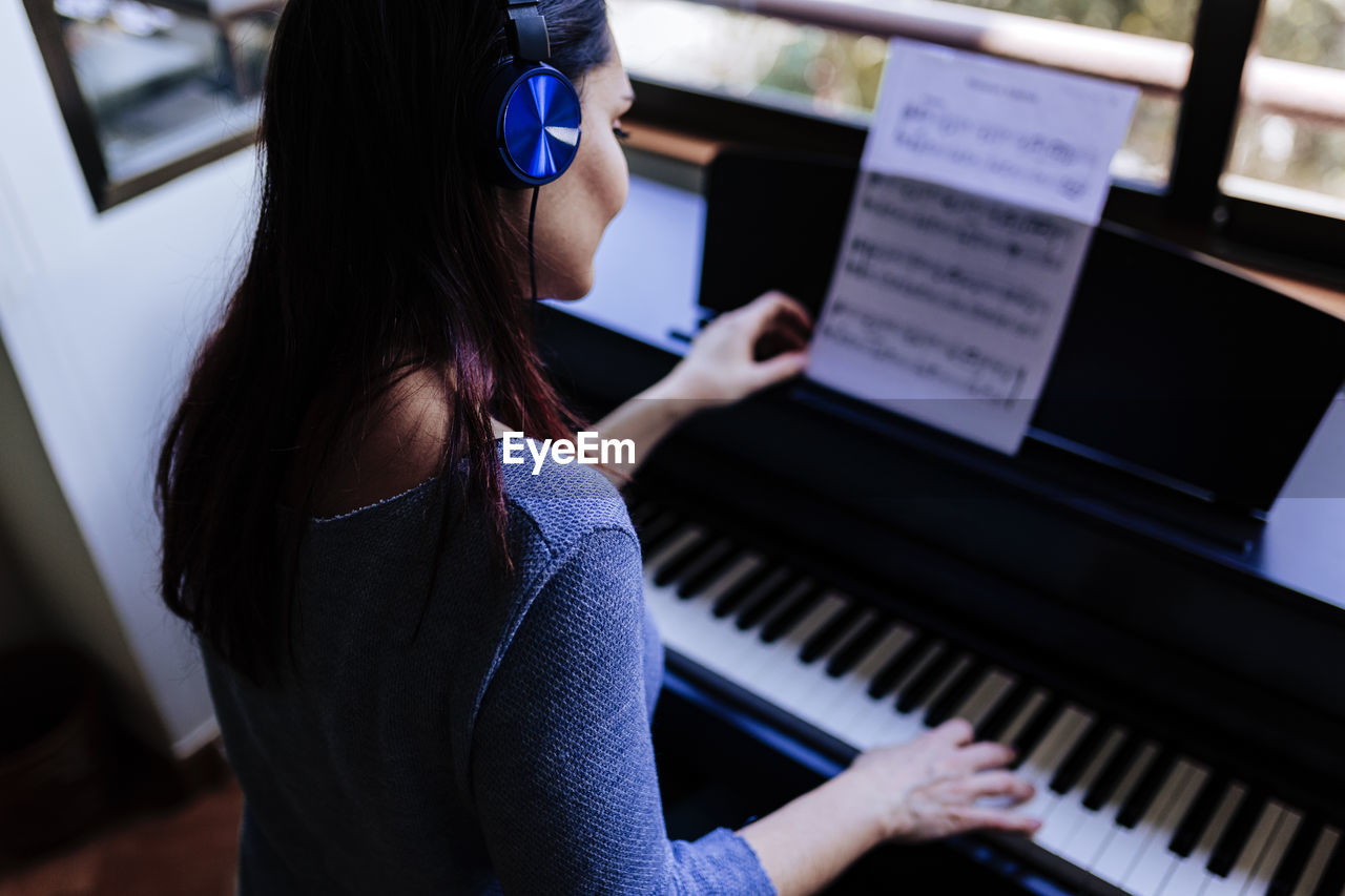 musical equipment, musical instrument, piano, music, sitting, real people, one person, indoors, lifestyles, arts culture and entertainment, waist up, casual clothing, leisure activity, women, focus on foreground, playing, skill, musician, adult, piano key, hairstyle, keyboard instrument