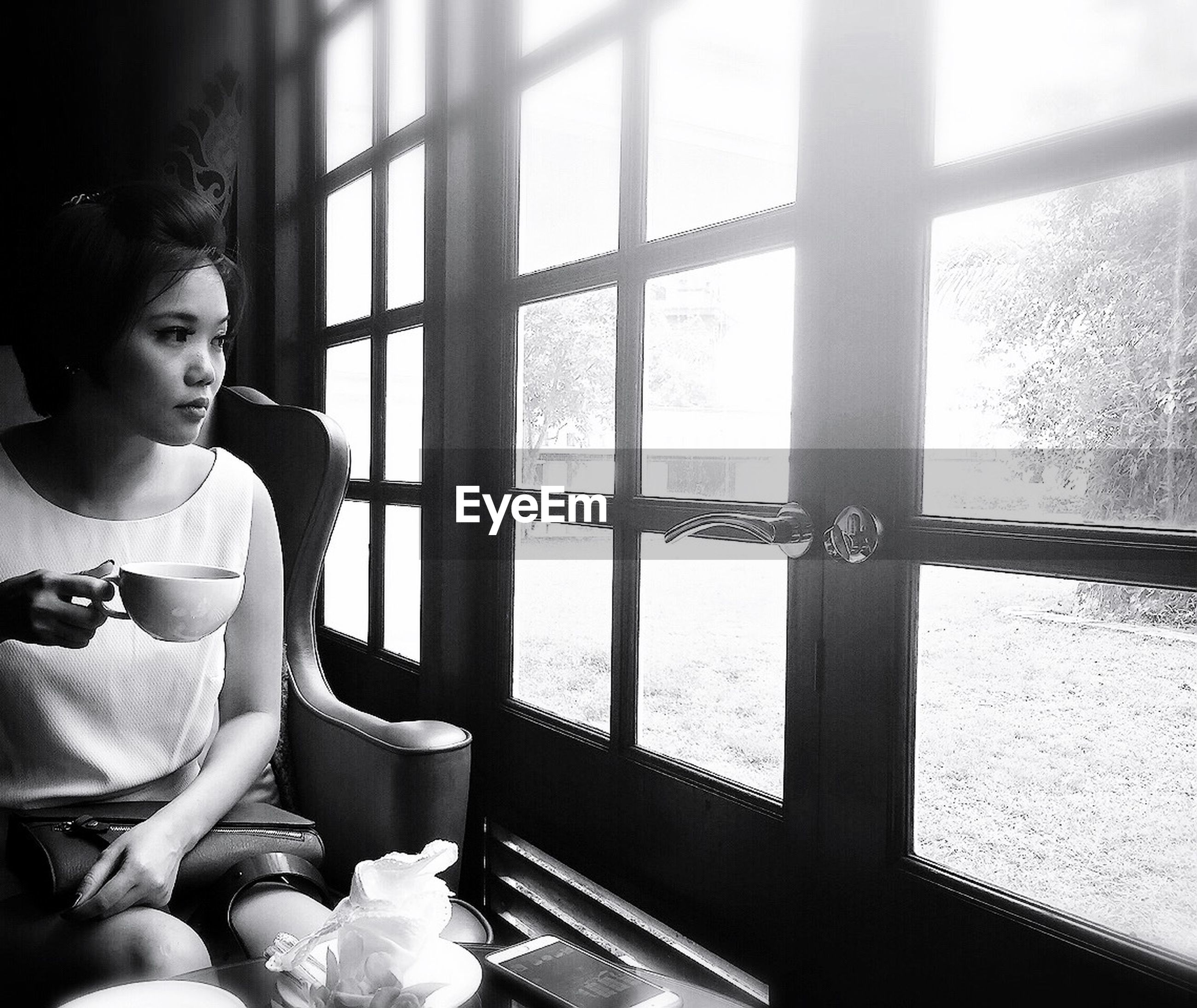 Thoughtful young woman having tea while sitting by window