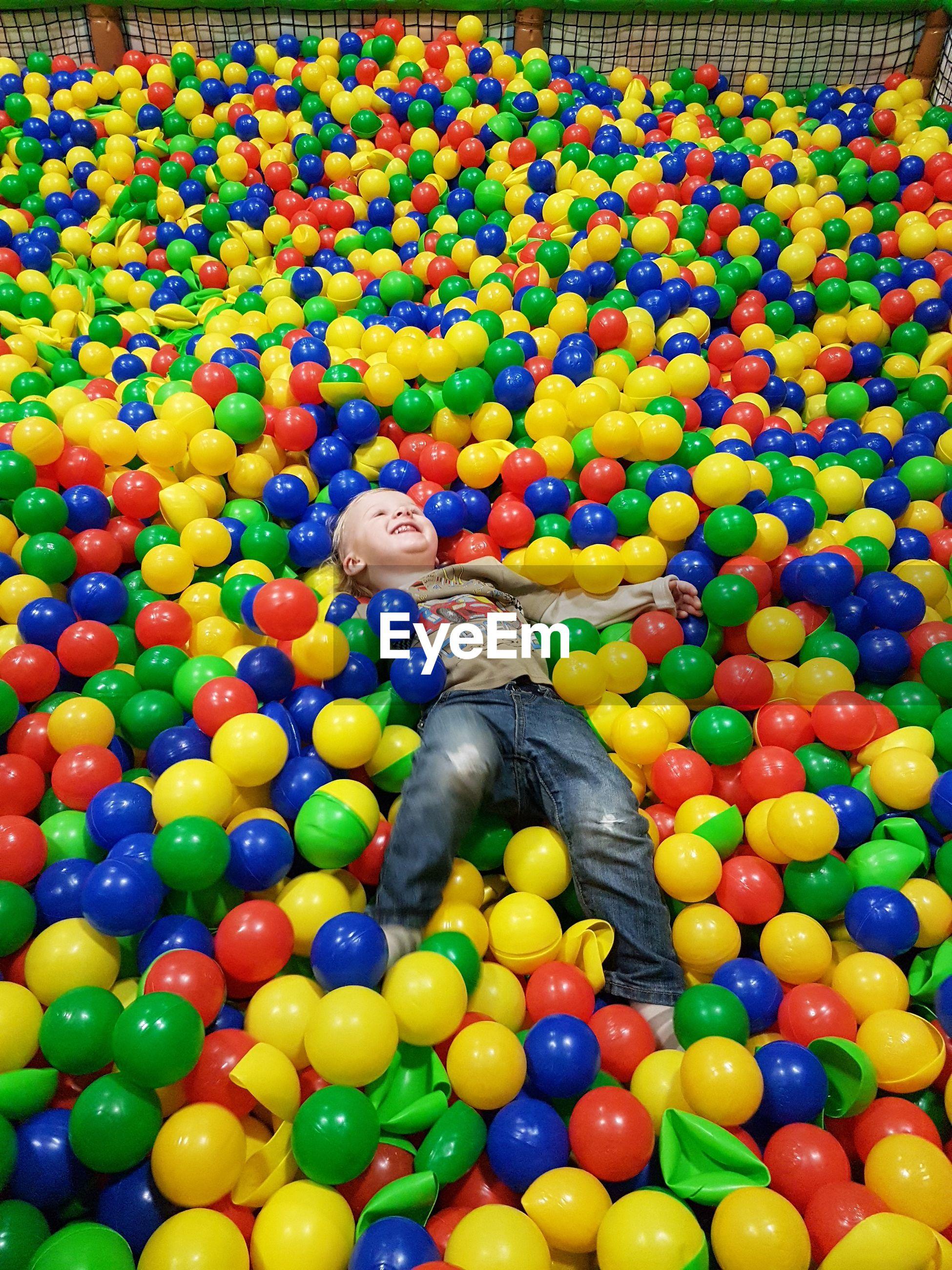 High angle view of boy lying on colorful ball pool