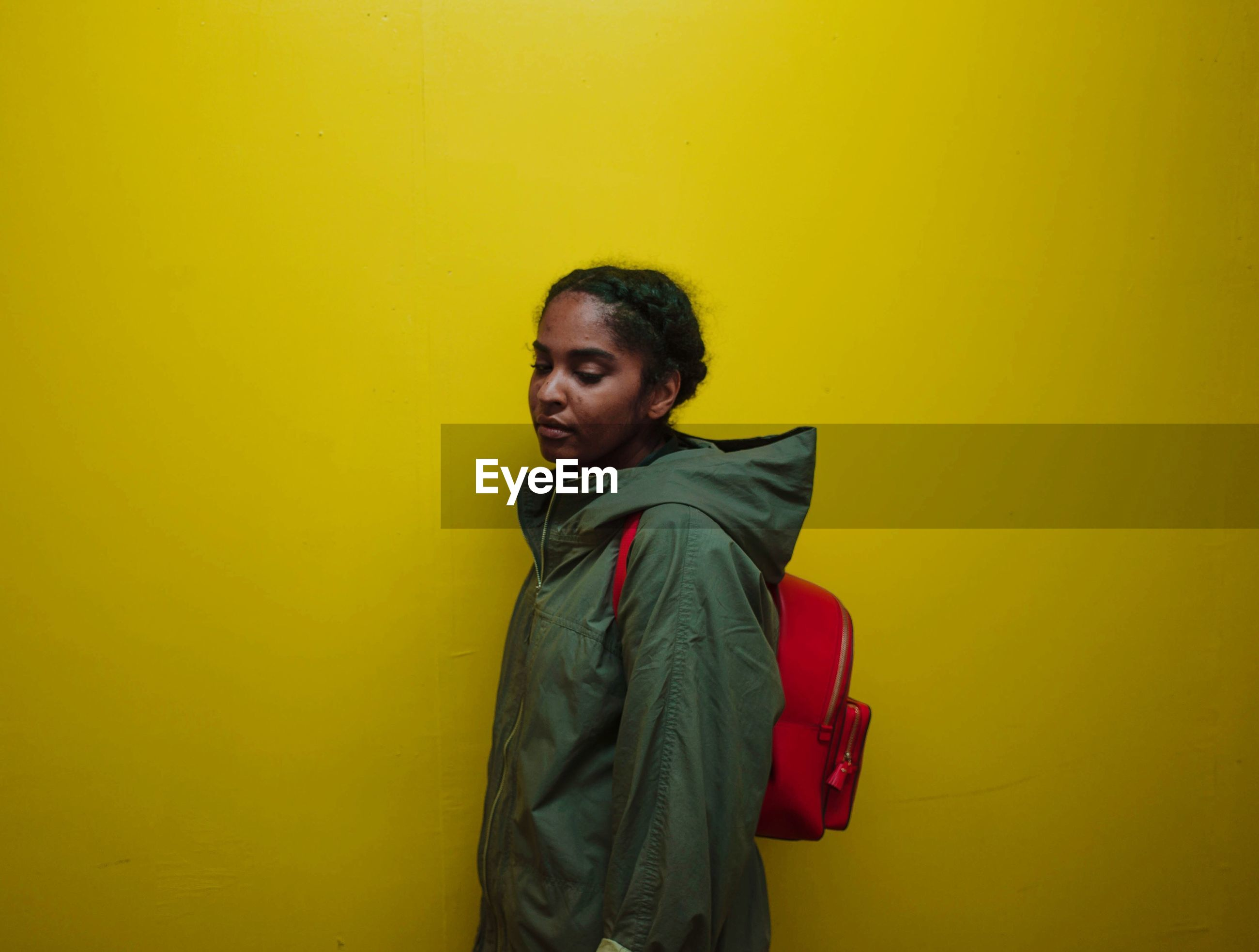 Teenage girl standing against yellow background