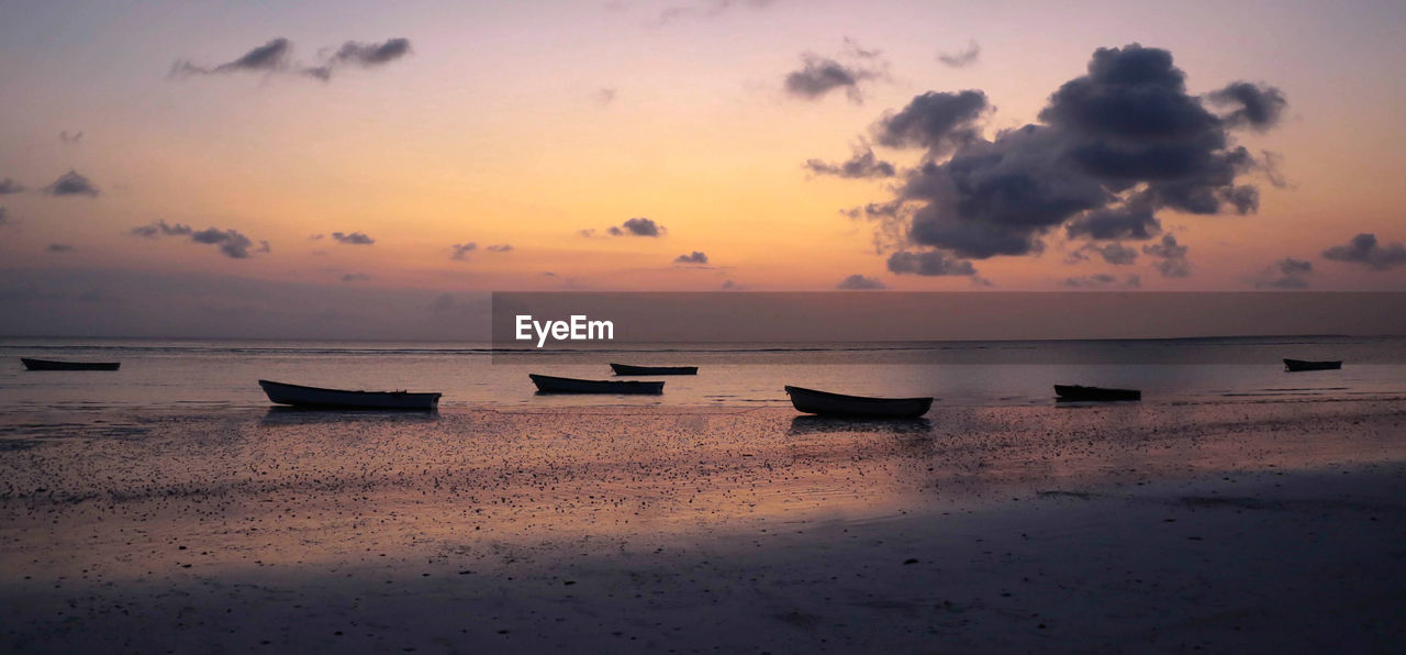 Silhouette Boats Moored At Beach During Sunset