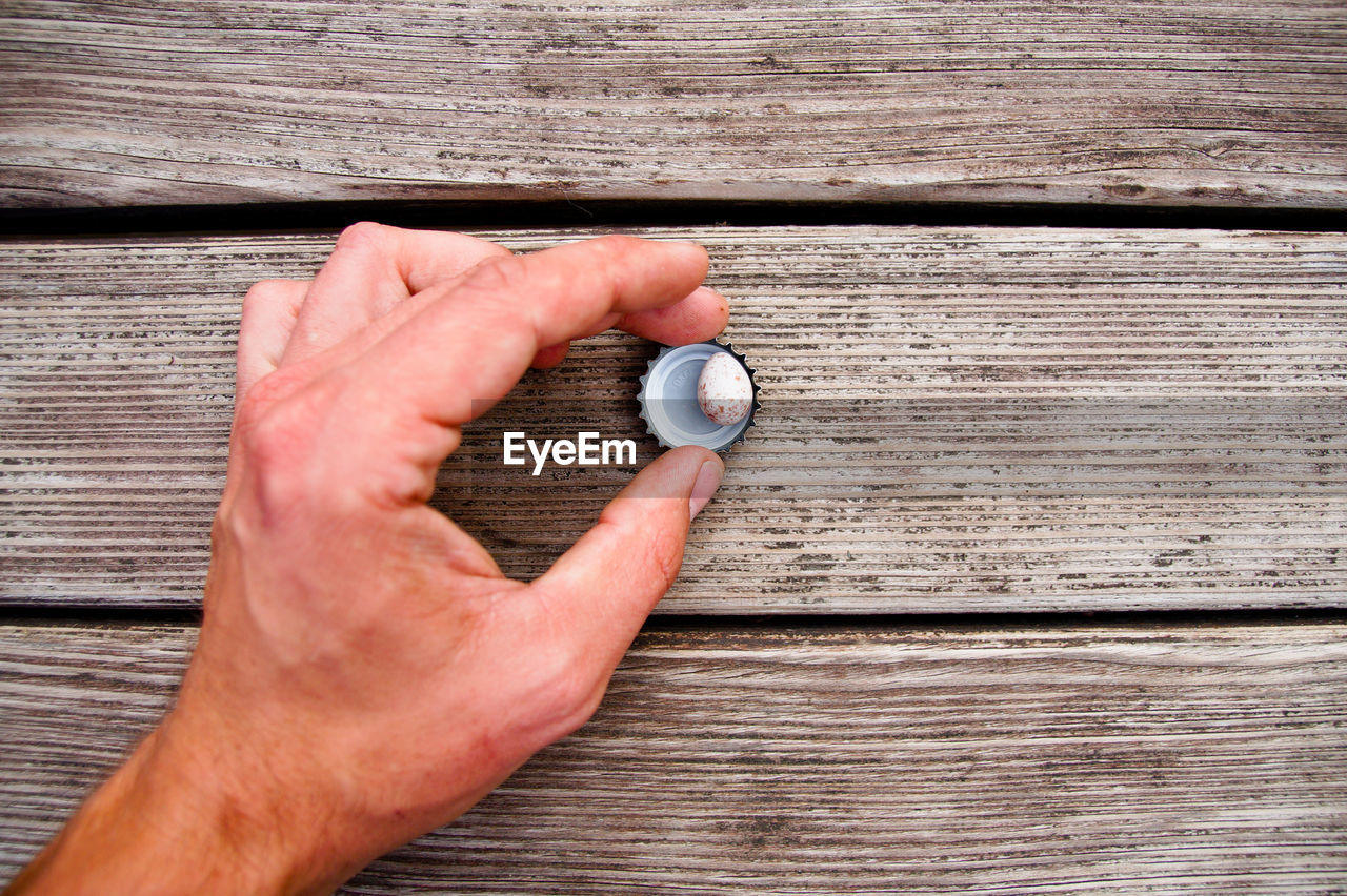 Cropped hand of man holding bottle cap on wooden table