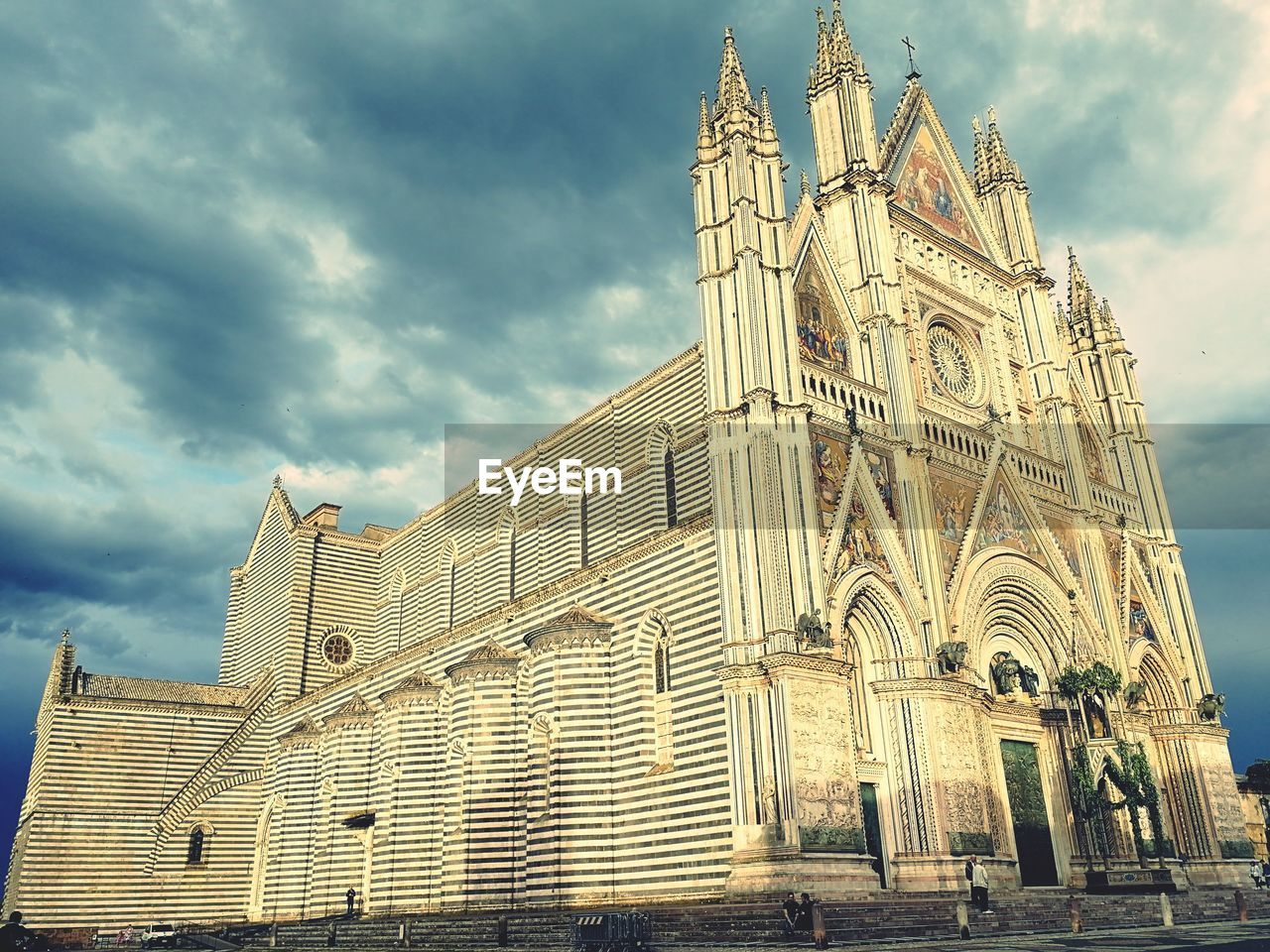 architecture, built structure, building exterior, sky, place of worship, cloud - sky, spirituality, belief, religion, building, low angle view, travel destinations, city, tourism, day, nature, no people, outdoors, spire, gothic style