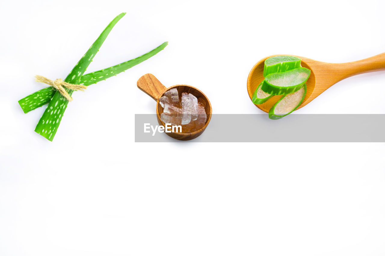 white background, studio shot, indoors, still life, freshness, close-up, green color, kitchen utensil, food and drink, eating utensil, food, no people, wellbeing, spoon, cut out, leaf, plant part, copy space, wood - material, vegetable, herb