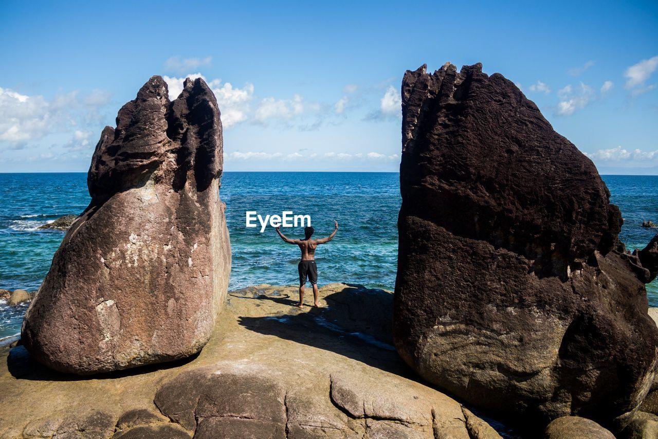 MAN LOOKING AT SEA BY ROCKS AGAINST SKY