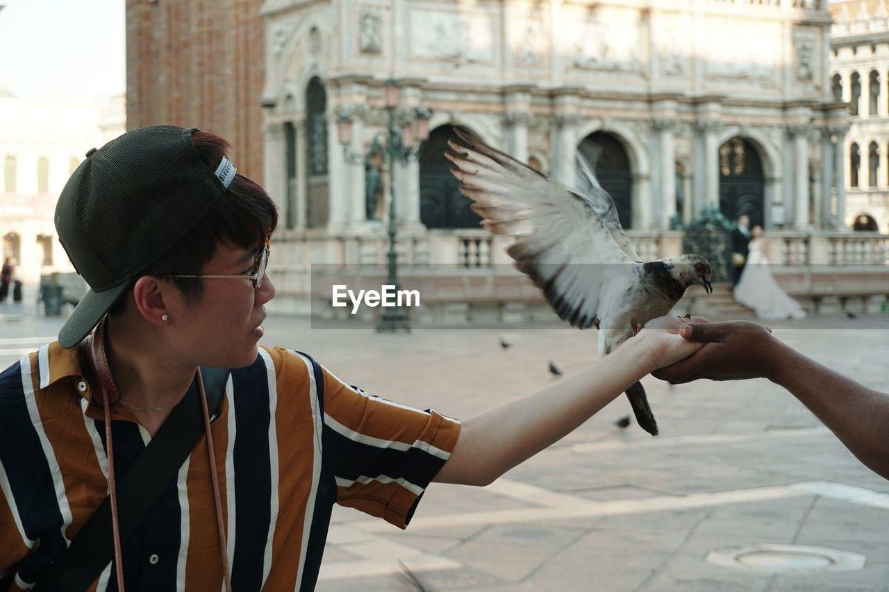 Woman Feeding Pigeon Outdoors