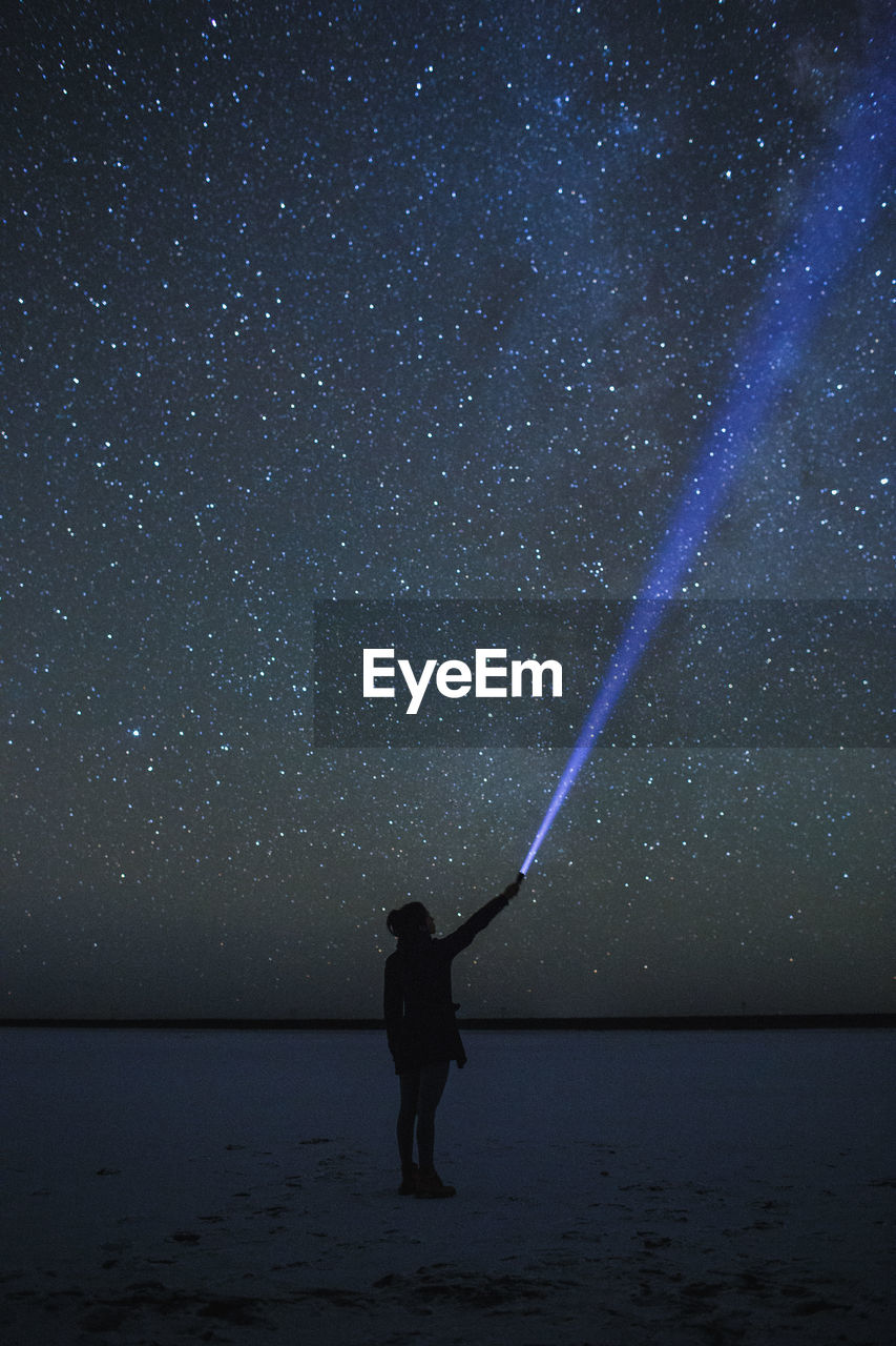 Full Length Of Woman With Flashlight Standing Against Star Field At Night