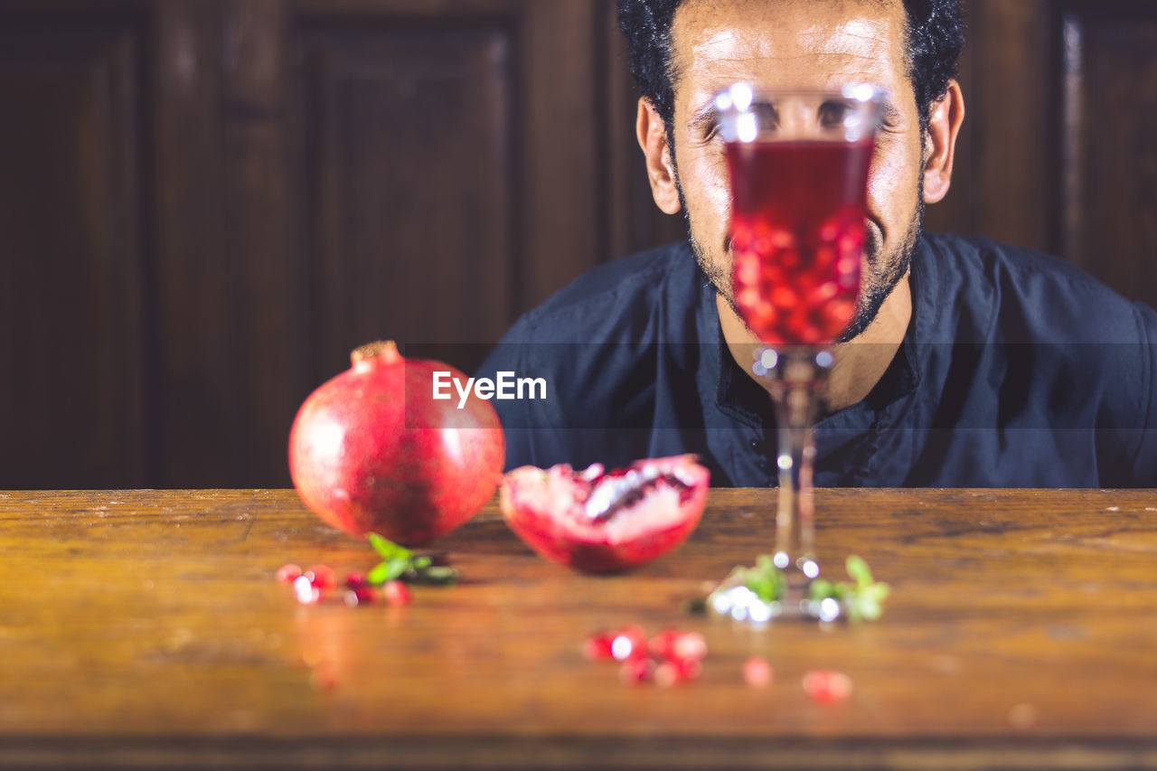 Close-Up Of Man With Red Wine On Table