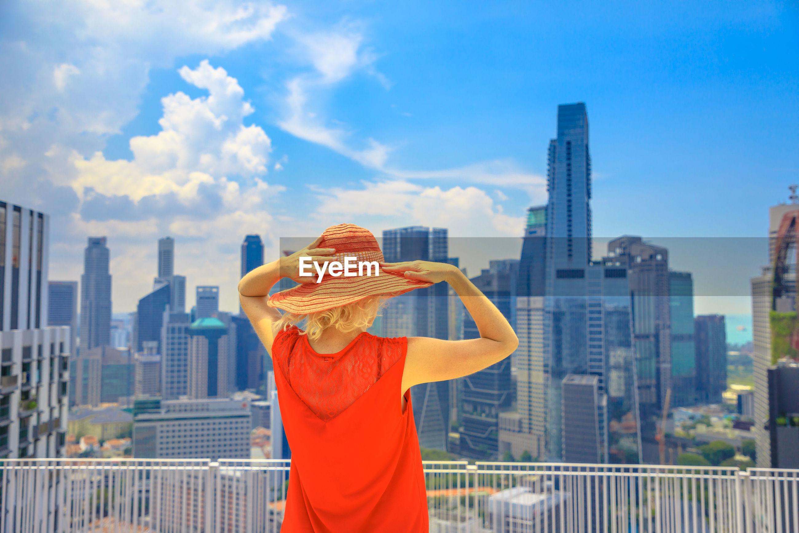 Woman standing against buildings in city