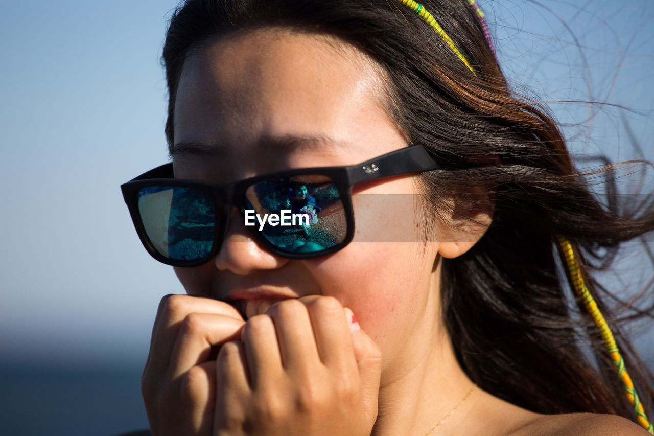 CLOSE-UP OF YOUNG WOMAN WITH EYEGLASSES AGAINST SKY