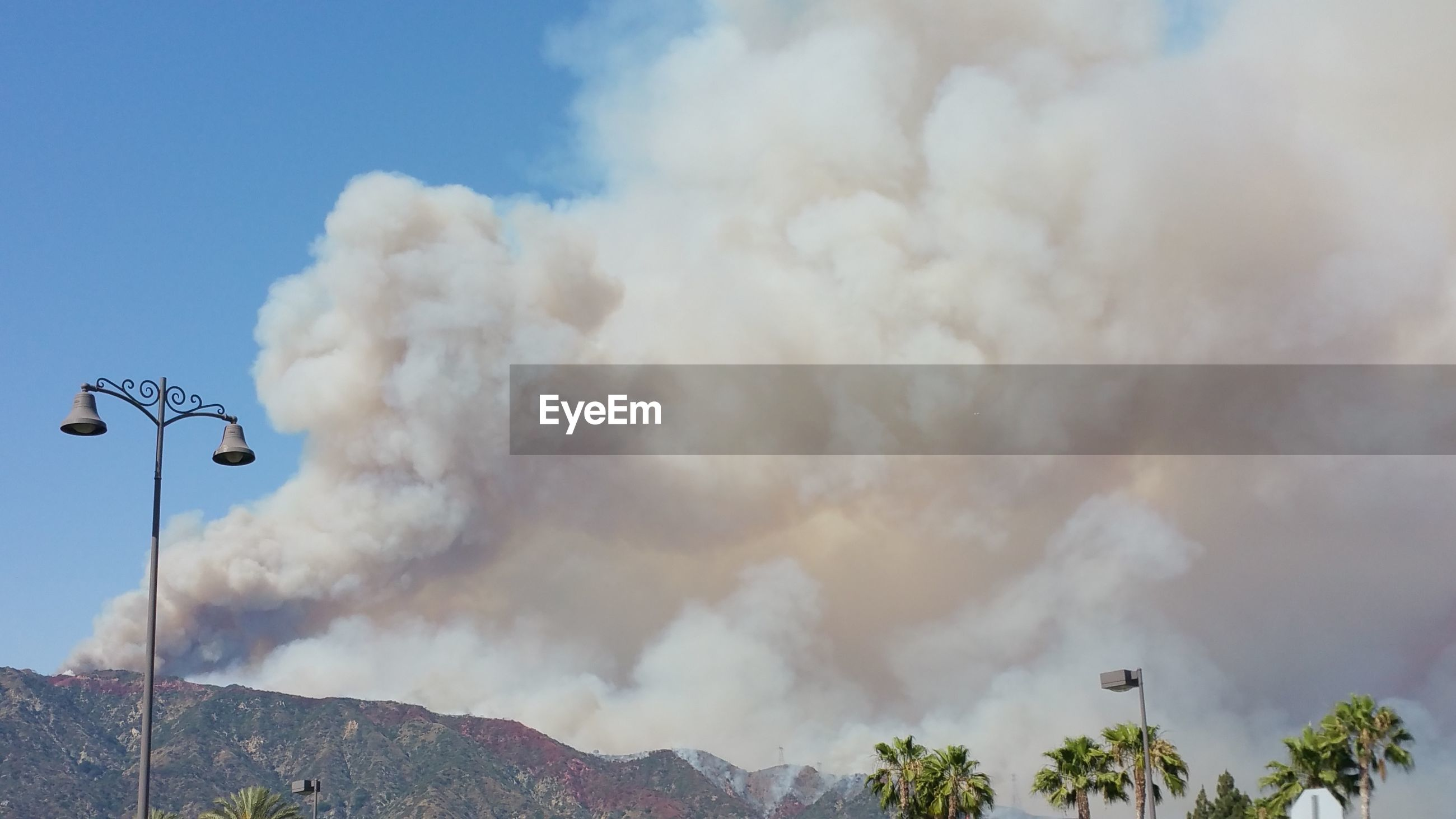 Scenic view of mountains against smoke in sky