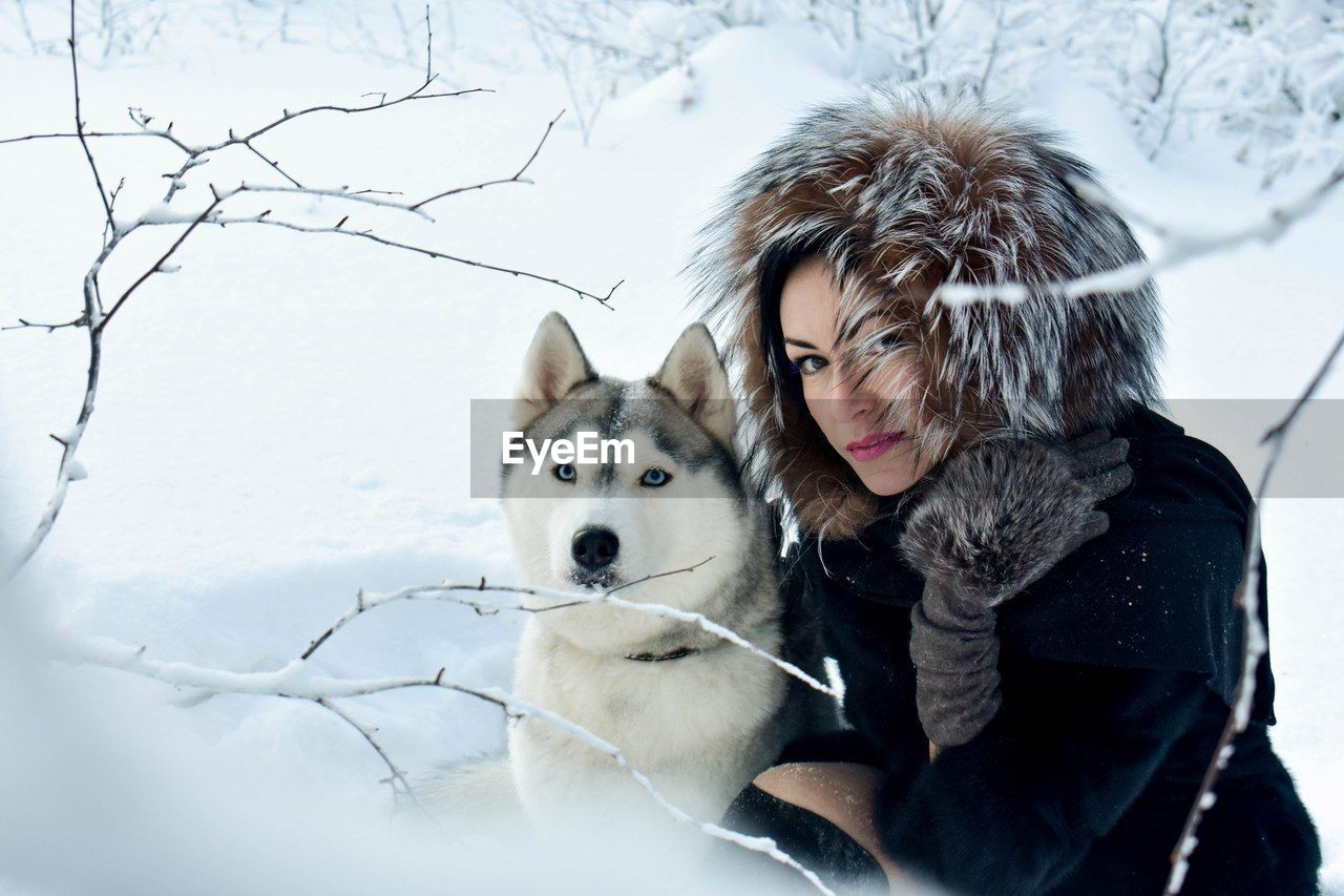 Portrait Of Young Woman With Dog In Snow