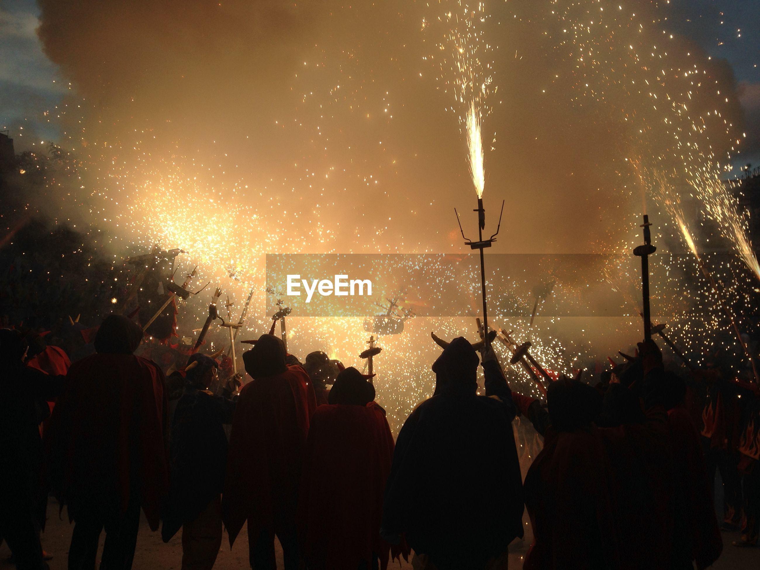 Silhouette people enjoying pagan festival at night