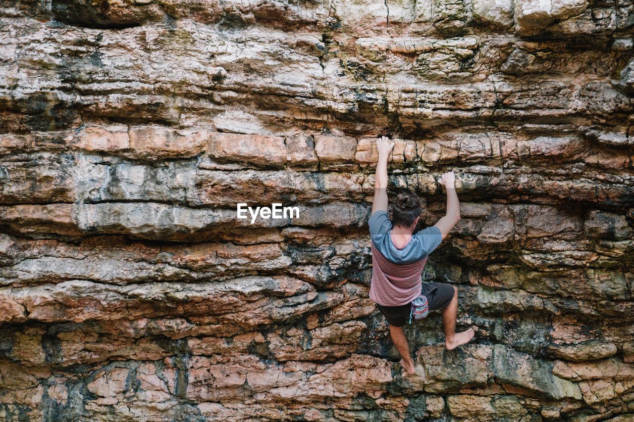 Rear View Of Young Man Climbing Mountain