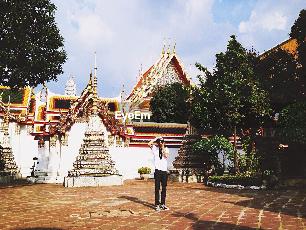 religion, place of worship, sky, spirituality, tree, real people, pagoda, architecture, built structure, day, cloud - sky, full length, travel destinations, men, gold colored, lifestyles, outdoors, one person, young adult, building exterior, people