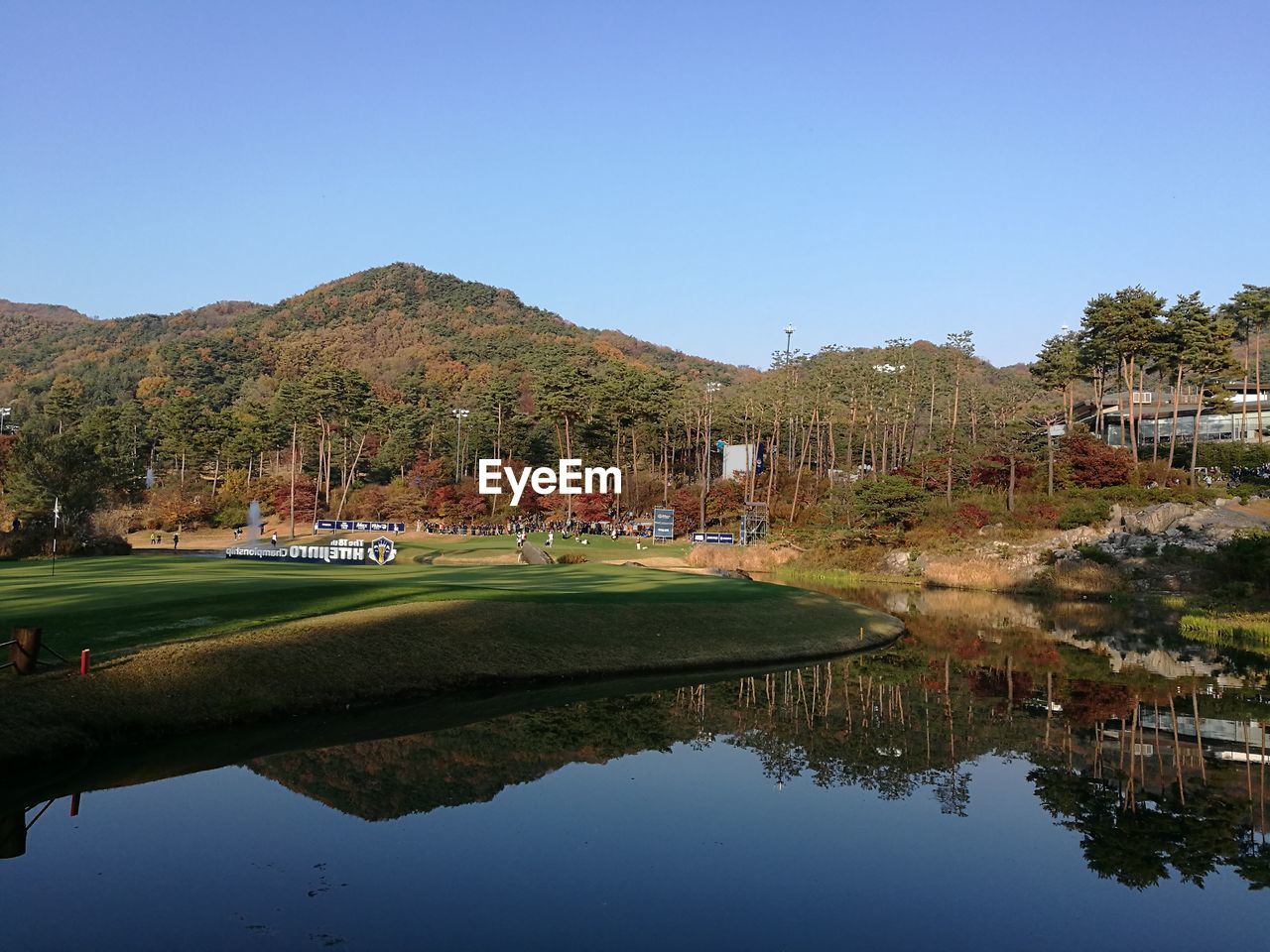 water, clear sky, reflection, copy space, waterfront, golf course, golf, building exterior, nature, outdoors, architecture, built structure, tree, day, tranquility, tranquil scene, mountain, tourist resort, beauty in nature, no people, scenics, blue, grass, sport, green - golf course, sky