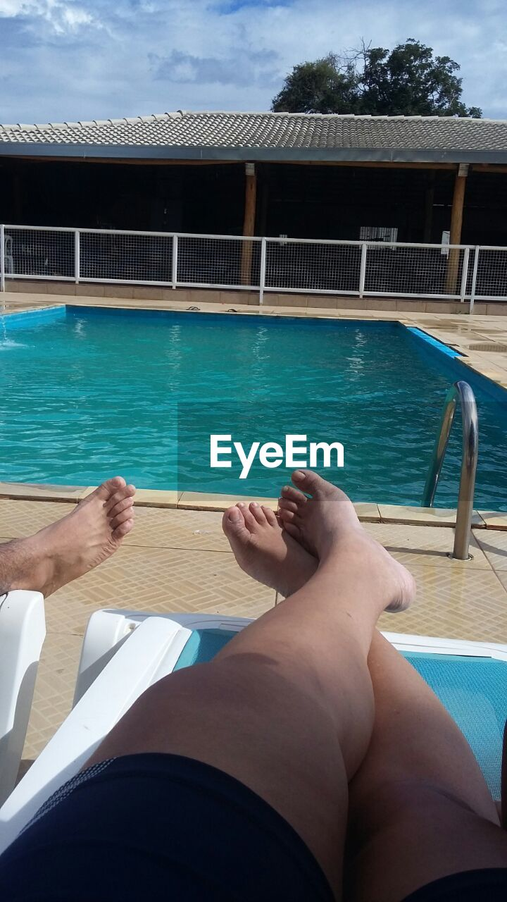water, human leg, human body part, low section, lifestyles, real people, one person, leisure activity, day, sea, sunlight, summer, barefoot, vacations, women, outdoors, swimming pool, relaxation, nautical vessel, blue, nature, sitting, human hand, sky, adult, people, adults only