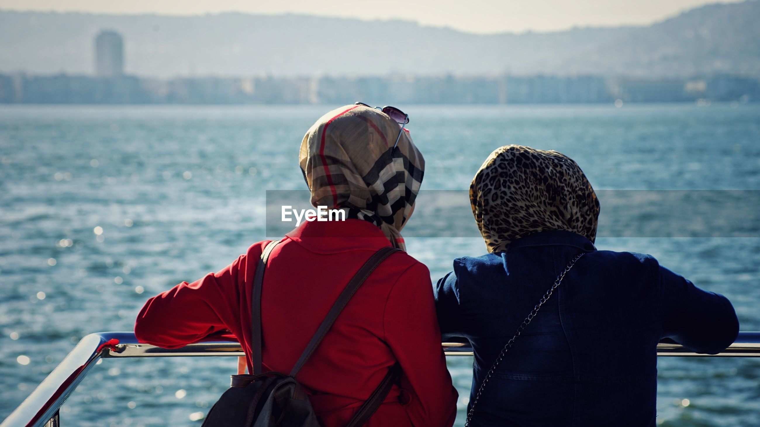 Rear view of women wearing headscarf looking at sea