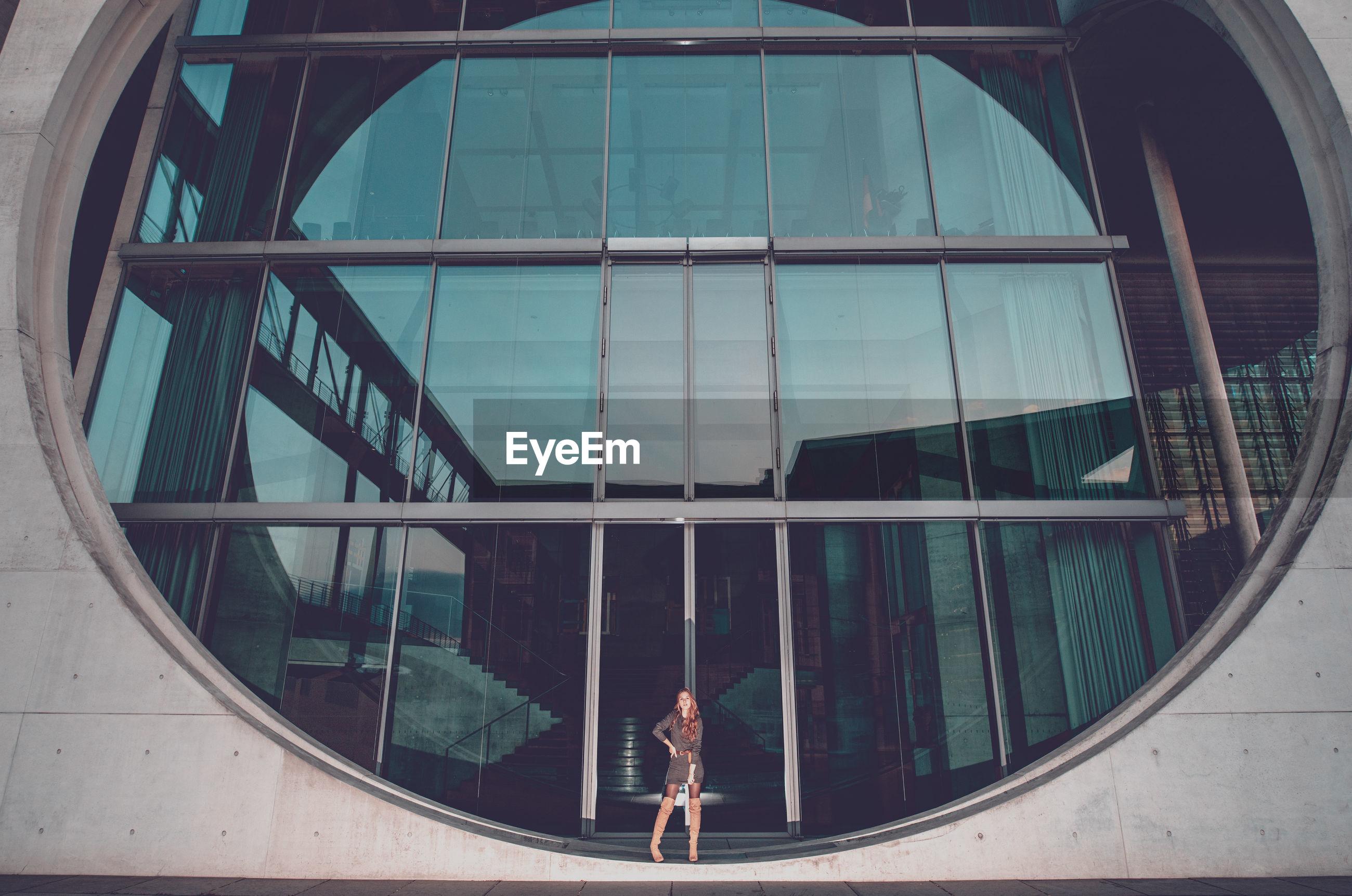 Young woman standing on circular window