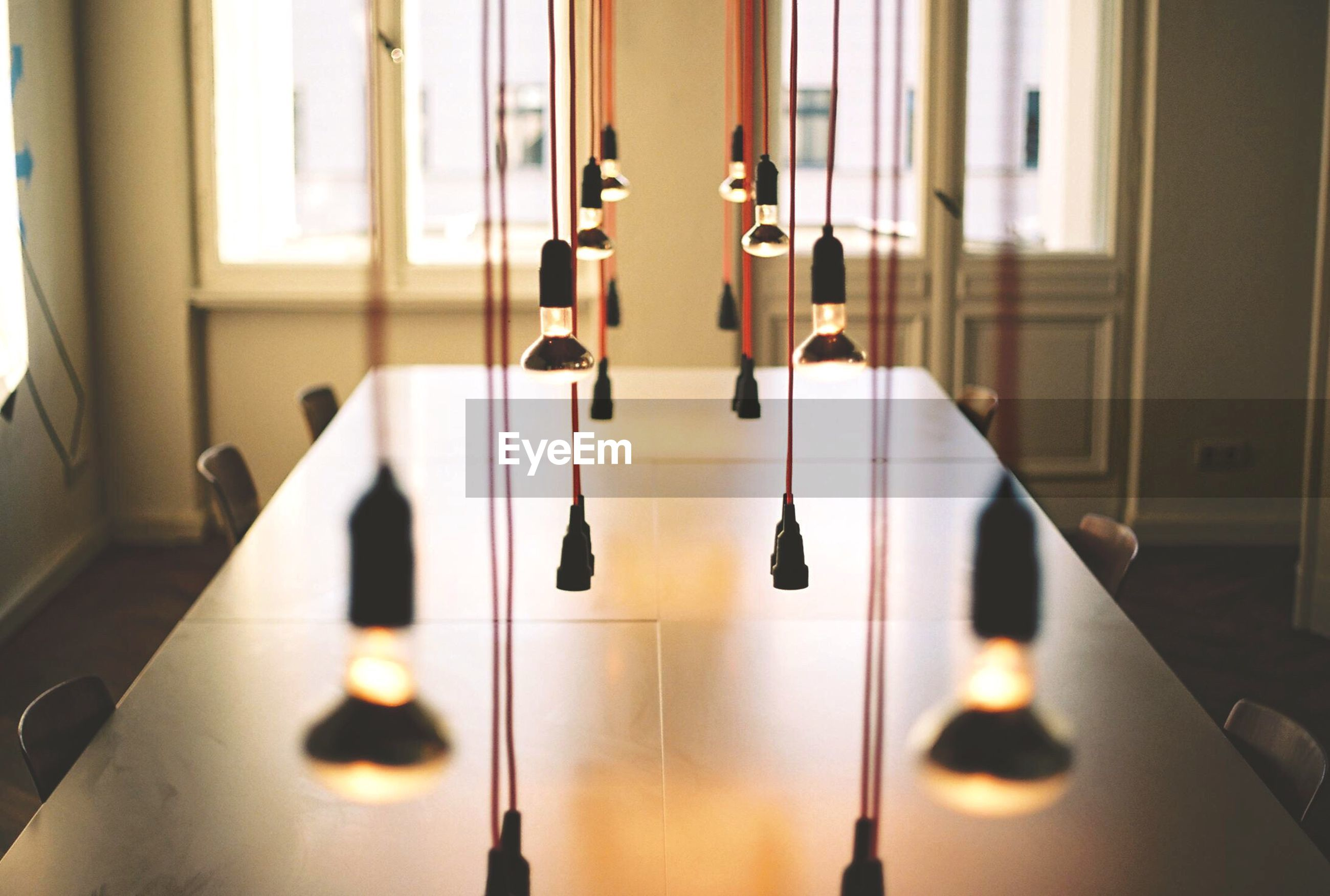Illuminated light bulbs above conference table