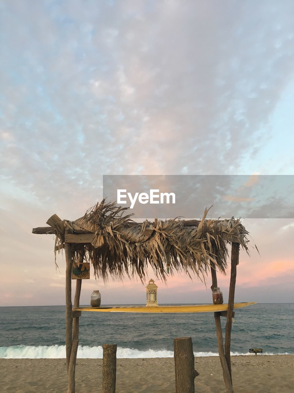 water, sea, sky, beach, land, cloud - sky, scenics - nature, beauty in nature, horizon over water, tranquil scene, tranquility, horizon, nature, thatched roof, sand, roof, no people, non-urban scene, palm tree, outdoors, wooden post