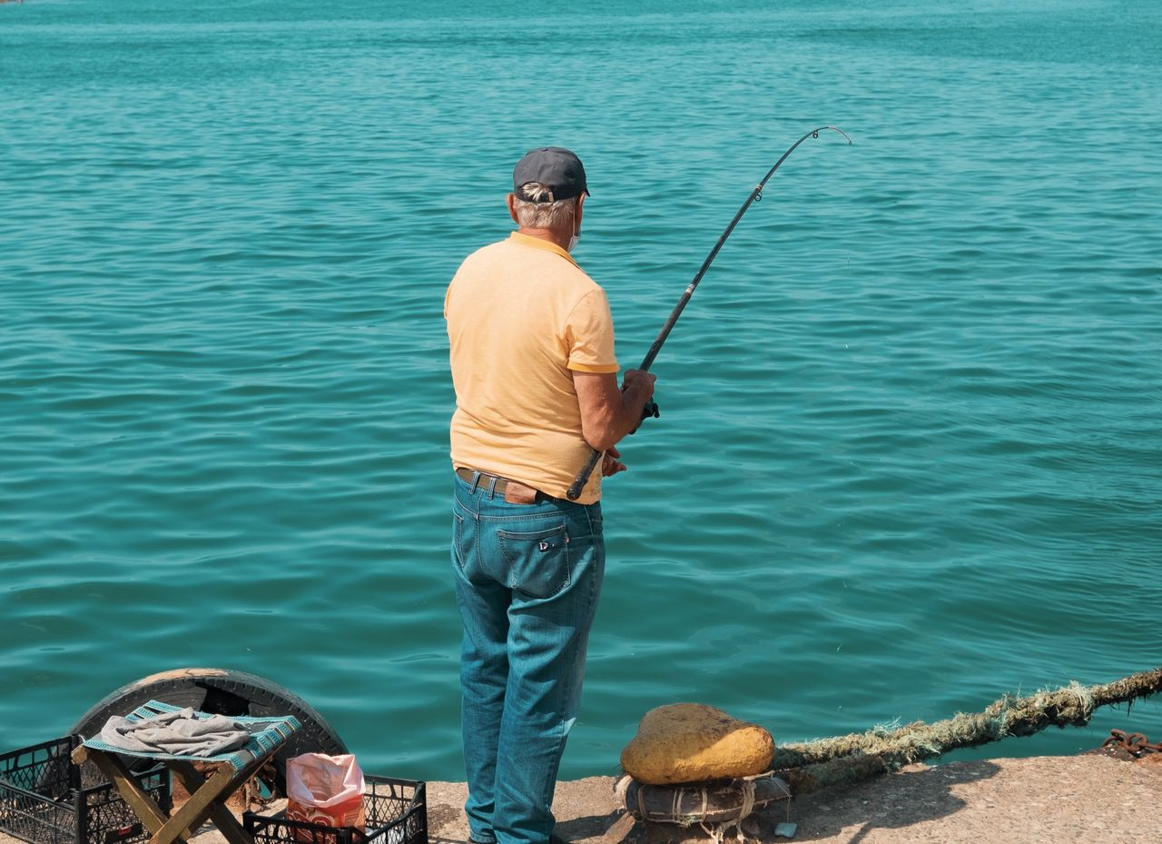 MAN FISHING ON SEA BY BOAT